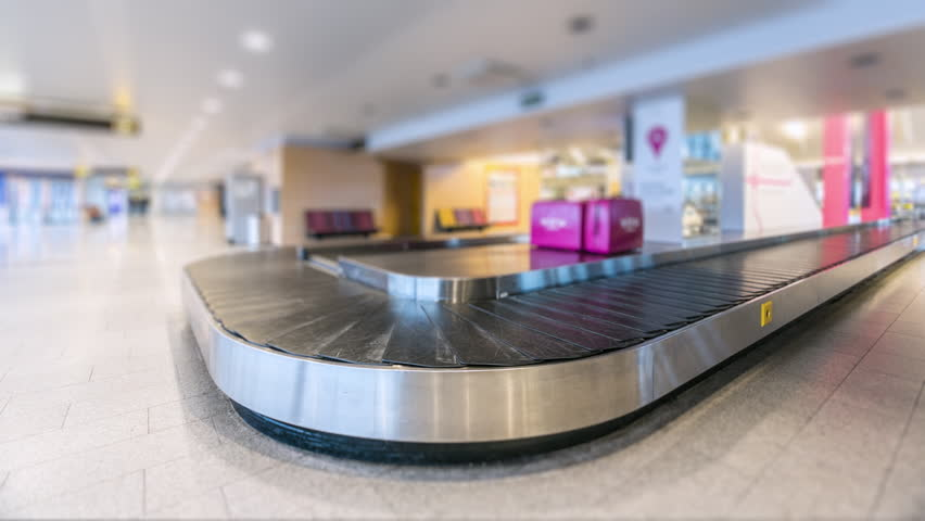 Time-lapse of modern airport luggage conveyor belt. People come from airplane, waiting and picking their bags and cases and leave. Tilt-Shift effect.