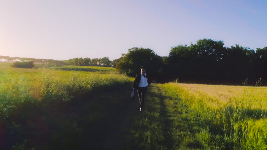 Running to freedom. Young businessman with elegant suit and briefcase in the middle of green golden wheat field in the nature at sunset aerial view drone slow motion