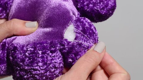 Closeup view of cute purple soft stuffed toy requiring to be stitched.