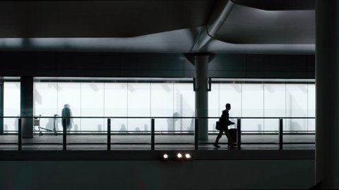 Heathrow Airport, UK 20 July 2016: Silhouette of passengers walking to the terminal.