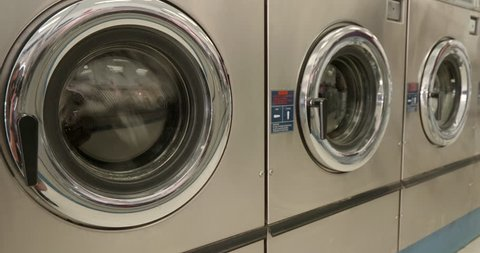 This is a shot of Dryers Drying Clothes in a Laundromat.