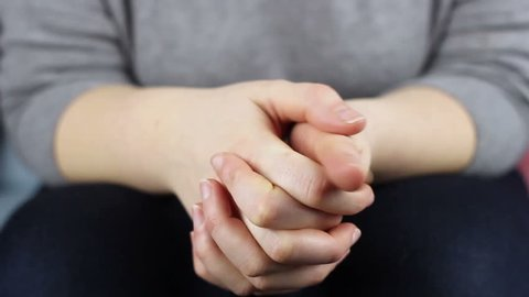 Close-up of wringing nervous woman hands.