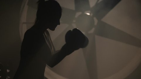 Silhouette woman fighter mma training punches with hands in boxing gloves