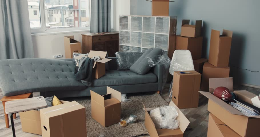 Spacious room with sofa, shelves and many boxes of new apartment. Move to apartment with modern repair in high-rise building.