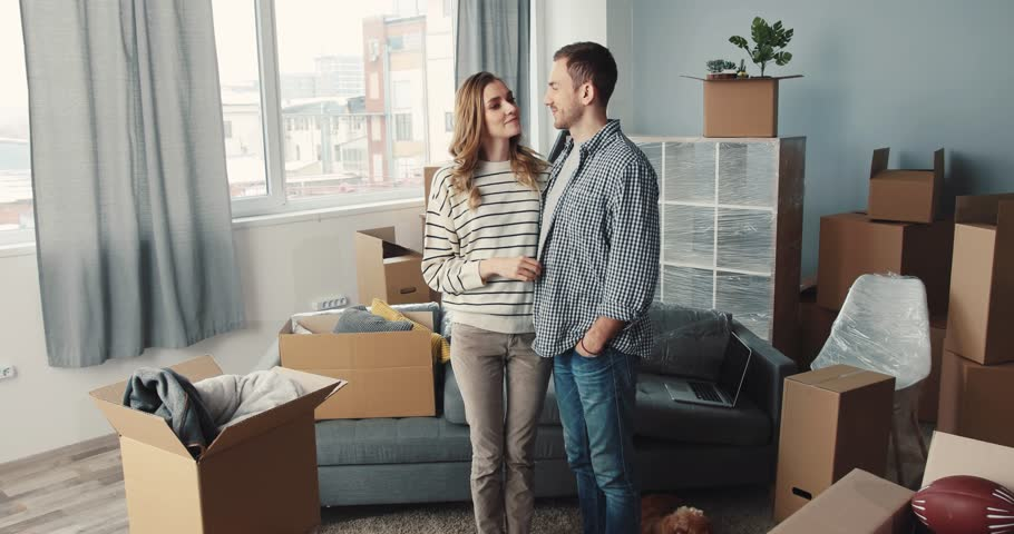 Young beautiful couple in love standing in center of room and looking at new apartment. Guy kissing girlfriend on cheek. Smiling. | Shutterstock HD Video #34760863