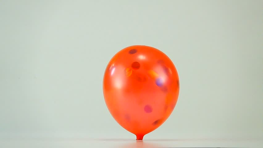 slow motion explosion of a red balloon on a white background