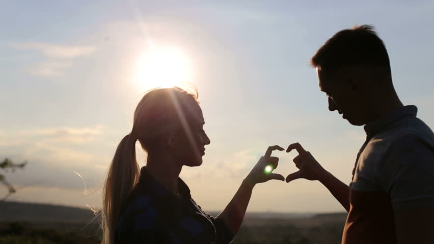 Silhouette of a loving couple who makes from the hands a heart shape. Silhouette of two hands join to form a heart shape in the sky with sun rays. Hands forming a heart shape on sunset, silhouette.