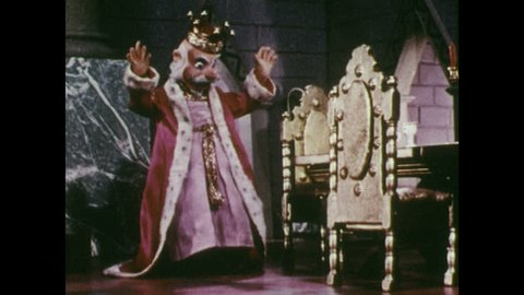 1950s: King touches his clothing. Clothing turns into gold. King clasps hands in delight. King sits at table. Girl walks into room and talks to man.