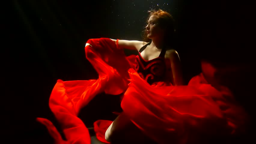 a woman with red hair is under water, a lady dressed in a lush red dress, she raises her hand up