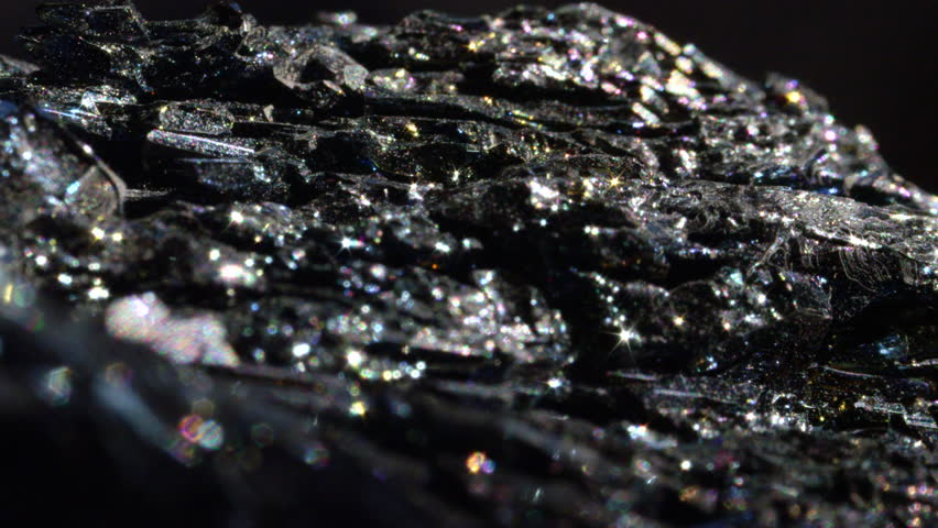 MACRO CLOSE UP: Shimmering dark Hematite with a metallic surface. Mineral form of iron oxide with intense sparkling detail. Radiant piece of haematite known for its earthy energy and use in feng shui