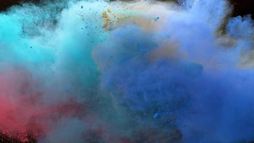 Colorful powder. orange powder, yellow powder, blue powder,Powder exploding against black background. Shot with high speed camera, phantom flex 4K. Slow Motion.