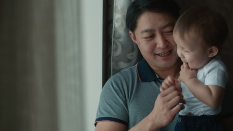 happy Asian family scene, father holding a baby in his arms by the window