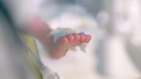 Feet and toes of an infant inside a ICU incubator.
