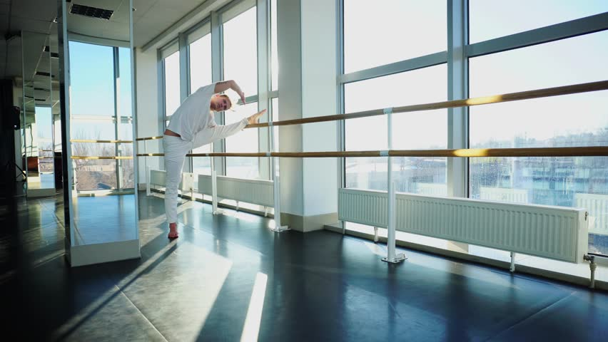 Gymnast train near ballet barre in sport gym, guy diligently doing stretching exercises for legs. Tattooed concentrated male wearing white sportswear sloping. Concept of well-equipped hall, sport | Shutterstock HD Video #34918558