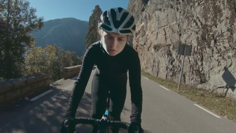Young female athlete, fit stong and healthy rides bicycle up steep mountain road on difficult training workout day, determined to reach goals and finish race as winner, inspiring outdoors activity