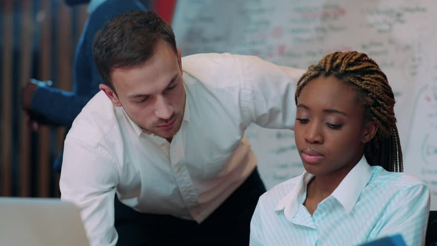 Young handsome Caucasian man talking with pretty African girl in beautiful modern office. Young people discussing upcoming business meeting. Close-up. | Shutterstock HD Video #34937566