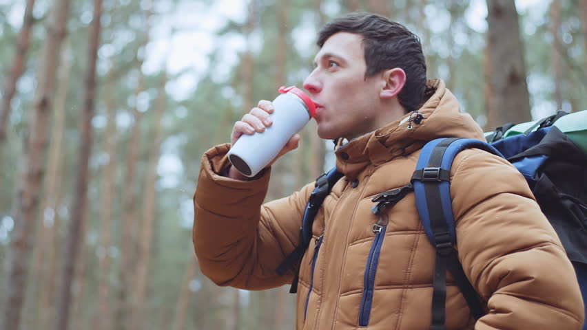Young man traveler drinking hot coffee or tea in thermos mug in forest, winter hike, cold season