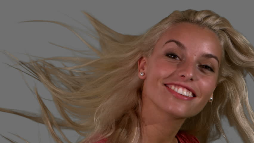 Attractive blonde shaking her hair on grey background close up in slow motion
