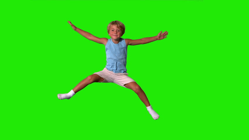 Boy jumping with limbs outstretched on green screen in slow motion
