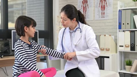 beautiful doctor checks up the good condition of kids injured arm. doctor and patient celebrate the hurt elbow recovery perfect hand high five together.