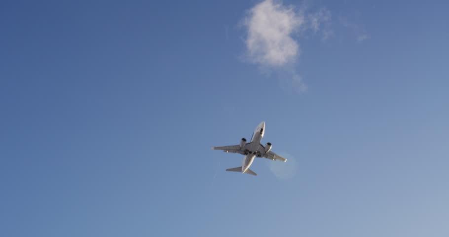 Jet plane approaching landing across blue sky, white clouds, slow-motion