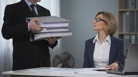 Female staff member of law firm overloaded with paper work, overtime labor