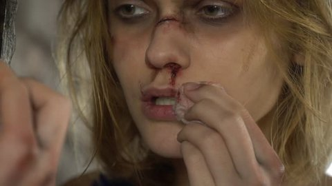 A beautiful girl wipes a napkin with blood from her lips