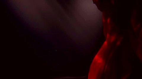 Long red dress is floating by itself underwater in dark.