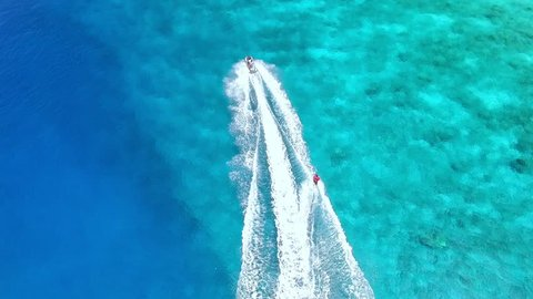 Ski jet sport in the blue, crystal clear sea. A 4K drone footage, shot from above.