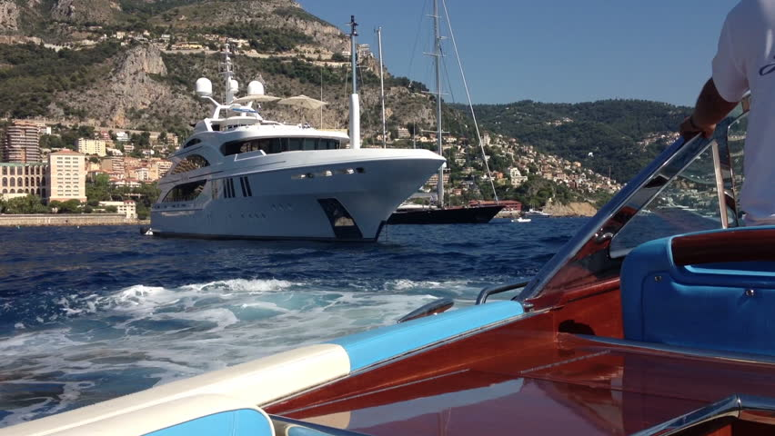 Cruising past luxury super yachts at anchor off Monaco
