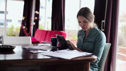 Businesswoman working with tablet computer and documents in home