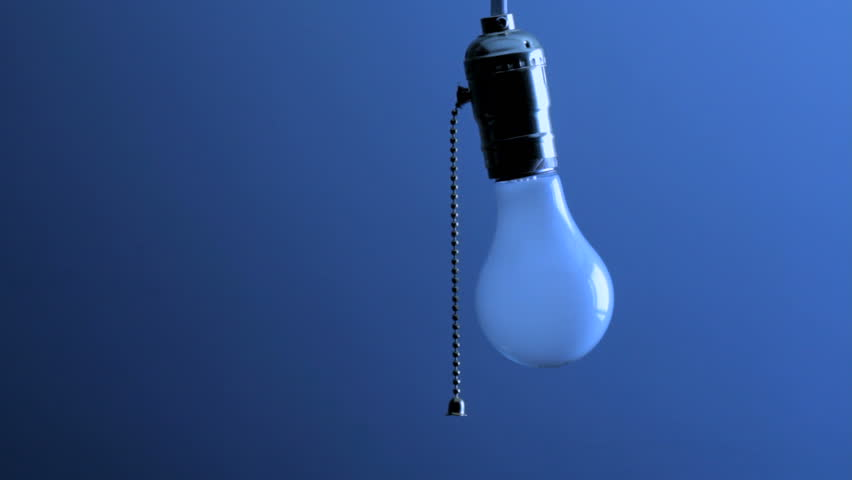 Woman's hand comes into frame, pulls chain and turns off hanging light bulb,
