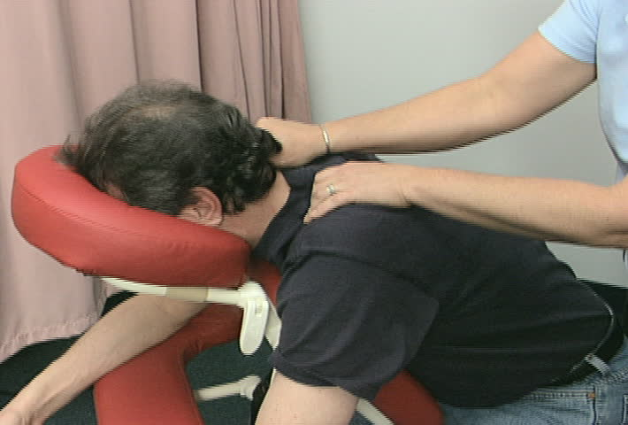 A static medium shot of a worker being given a massage at his workplace.
