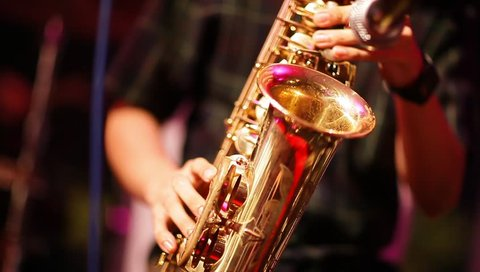 Musician is playing on saxophone in concert. Close-up on fingers pressing the keys of the instrument
