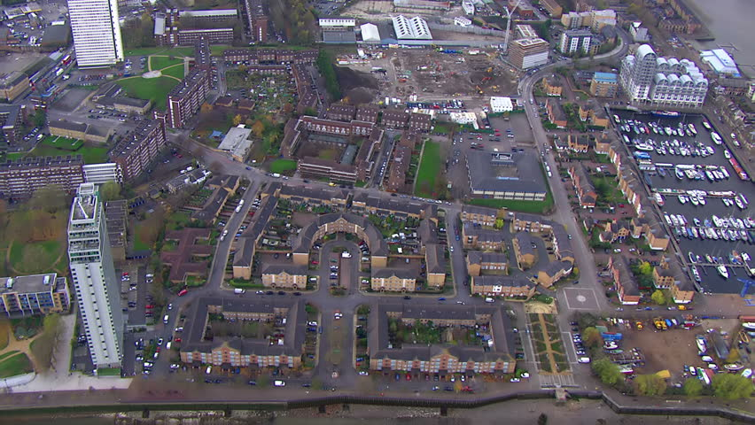 Aerial view over a London district, showing residential tower blocks and other housing, as well as green spaces and roads and other industrialised  areas.