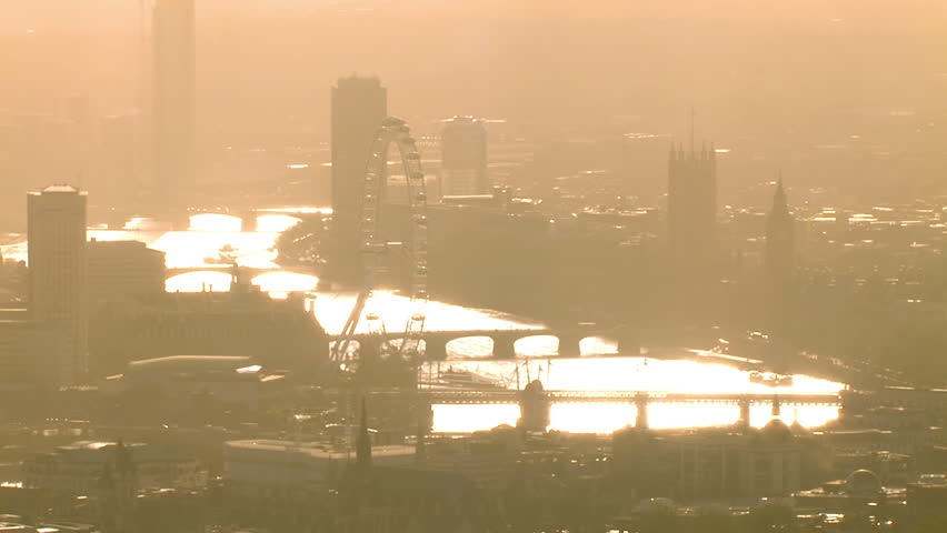 Aerial shot passing over the River Thames near Westminster on a hazy autumn morning. Many distinctive London landmarks can be seen.