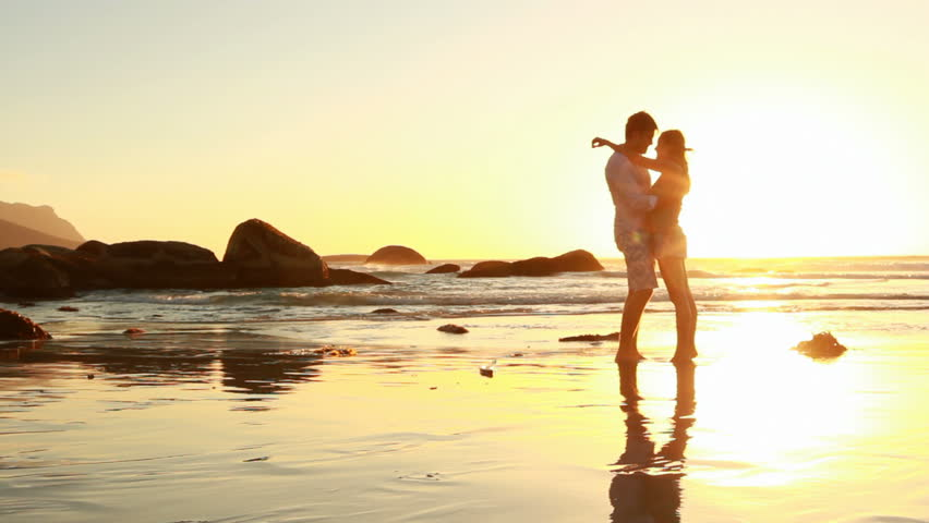 Passionate couple holding each other on the beach at sunset.