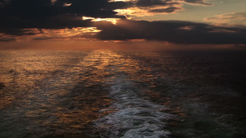 View from the stern of a cruise ship on the multicolored sunset on a cloudy sky.