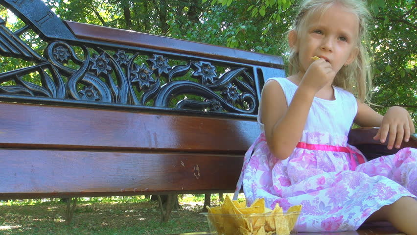 Little Girl Eating Cornflakes on Bench in Park, Child Eats Cereals, Children