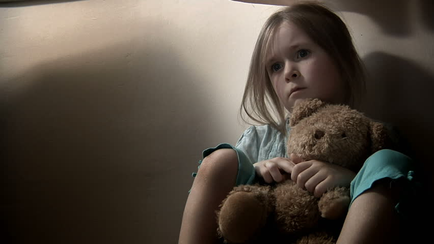 Sad little girl, clutching her teddy bear. Intentionally desaturated.