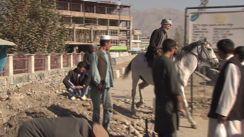 Faizabad, Afghanistan - November 7, 2010:  Man on horse riding on main street in Fayzabad, Afghanistan.
