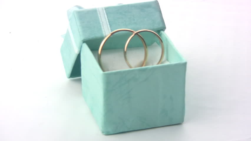 Two wedding rings rotate in the green box with a bow