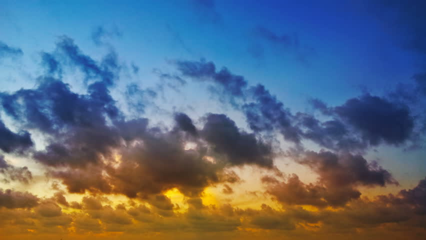 1920x1080 video - Time lapse clip of red, blue and yellow fluffy clouds over blue sky on sunset