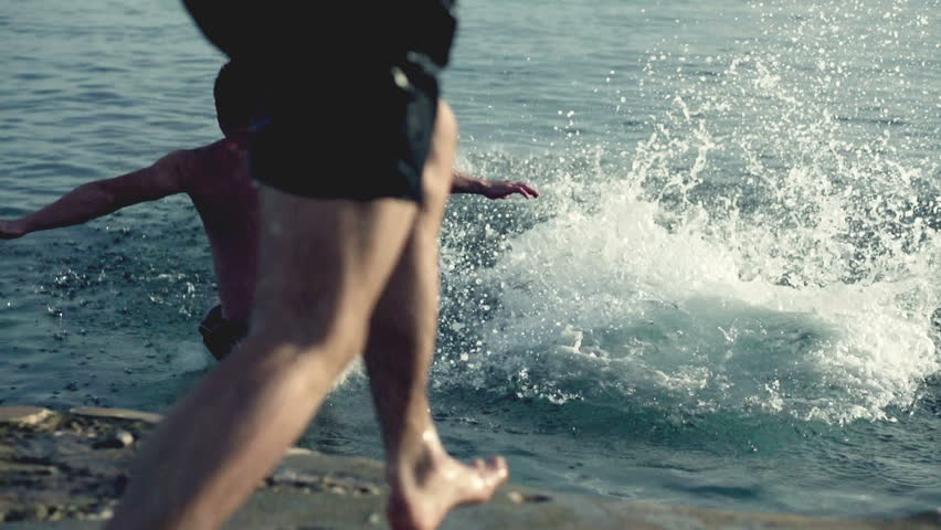 Young three men jumping into the sea, slow motion shot at 240fps