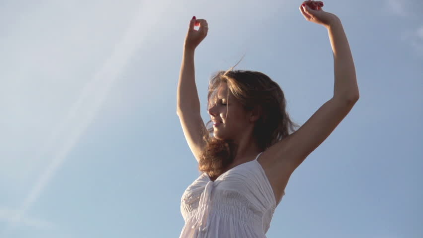 Happy beautiful woman stretching towards the sky, slow motion shot at 120fps