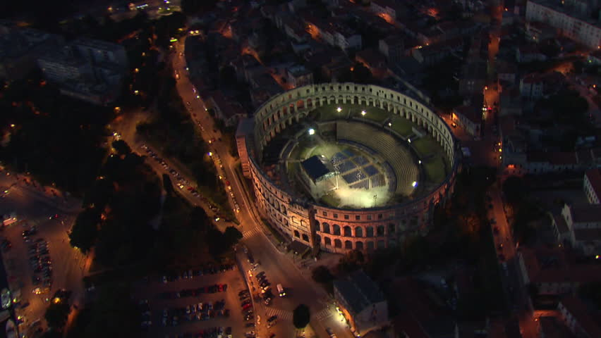 City of Pula and the Arena at night. Aerial helicopter shot.