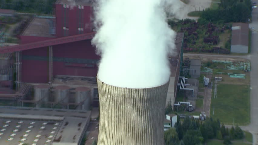 A Power Plant and its cooling tower with steam rising from it and tall flue gas