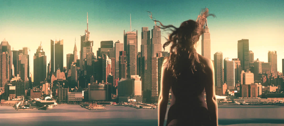 woman overlooks Manhattan blowing up, engulfed in flames, smoke.