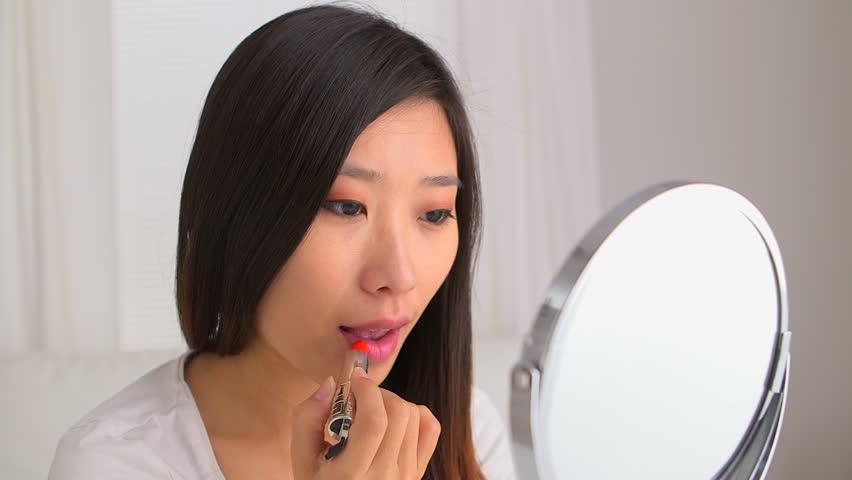 Chinese woman putting on lipstick