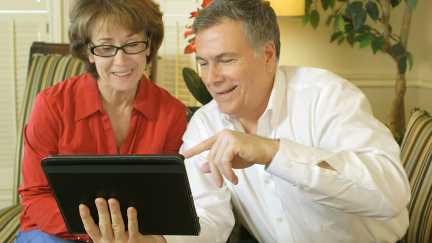 A mature couple using an electronic tablet with a web camera to see and be seen as they talk to their grandchildren on the other end.